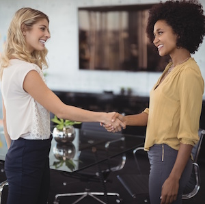 Businesswomen shaking hands in meeting room at creative office